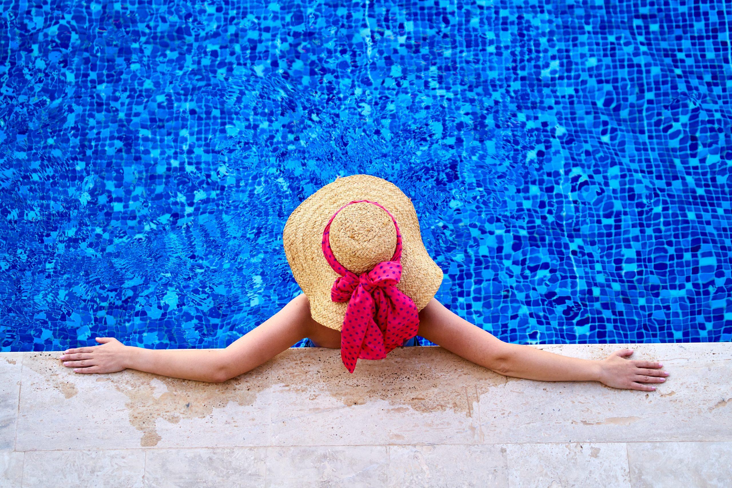 donna con cappello di paglia e fiocco rosso in piscina